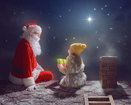 Merry Christmas and happy holidays! Cute little child girl and Santa Claus sitting on the roof and looking at snowfall. Christmas legend concept. Stock Photo