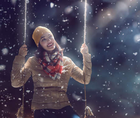winter vacation: Beautiful young woman on a swing on snowy winter walk. Outdoor fun for winter vacation. Portrait girl on dark background. Stock Photo