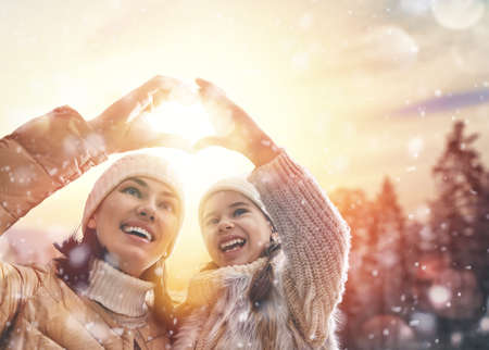 heart in hand: Happy loving family! Mother and child girl having fun, playing and laughing on snowy winter walk in nature. Frost winter season. Mom and kid making hand heart in evening.