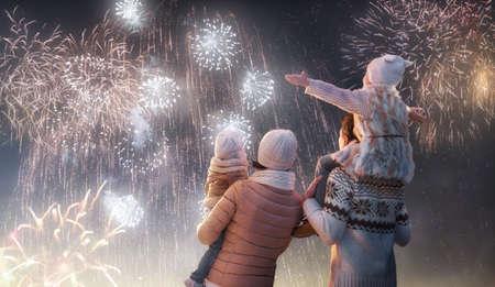 fuegos artificiales: Fiesta del Año Nuevo. Familia feliz, padres e hijas muchachas de los niños están viendo los fuegos artificiales. El niño se sienta en los hombros de su padre en caminata del invierno cubierto de nieve en la naturaleza. Vacaciones temporada de invierno.