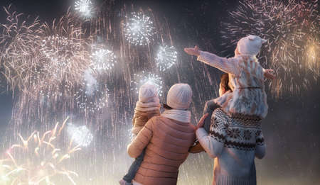 New Year holiday. Happy family, parents and daughters children girls are watching fireworks. The child sits on the shoulders of his father on snowy winter walk in nature. Holidays winter season.