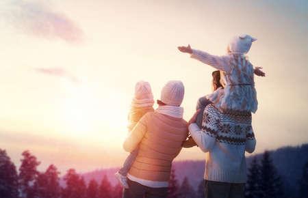Gelukkige familie bij zonsondergang. Vader, moeder en twee kinderen dochters plezier hebben en spelen op besneeuwde winter wandeling in de natuur. Het kind zit op de schouders van zijn vader. Frost winterseizoen.