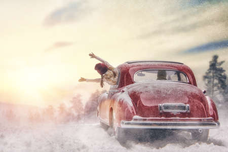 Toward adventure! Happy family relaxing and enjoying road trip. Parent, child and vintage car on snowy winter nature background. Christmas holidays time. Foto de archivo