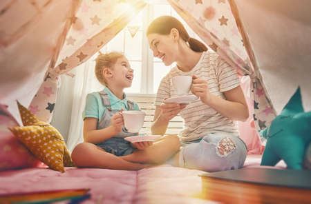 행복 한 사랑 가족. 어머니와 그녀의 딸 소녀 티 파티를 연주하고 어린이 방에서 컵에서 차를 마신다. 재미 엄마와 실내 사랑스러운 아이 재미.