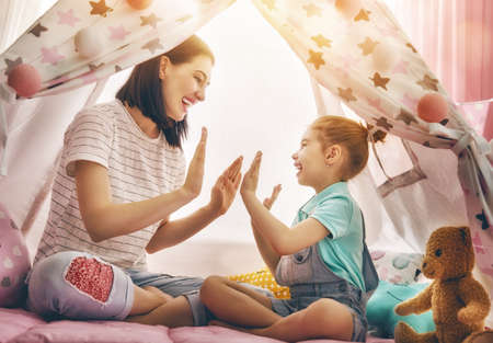 Happy loving family. Mother and her daughter girl play in children room. Funny mom and lovely child having fun indoors.