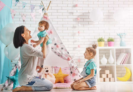 Happy loving family. Mother and her daughters girls play in children room. Funny mom and lovely children are having fun indoors. Stock Photo