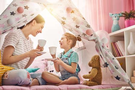 Gelukkig liefdevolle familie. Moeder en haar dochter meisje spelen tea-party en thee drinken uit bekers in de kinderkamer. Grappige mamma en mooie kind plezier binnenshuis. Stockfoto