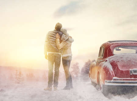 Toward adventure! Happy loving couple is relaxing and enjoying road trip. Young woman, man and vintage car on snowy winter nature background. Christmas holidays time.