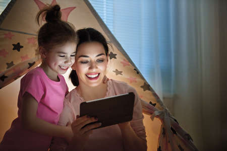 child smile: Happy loving family. Young mother and her daughter girl play in children room at the bedtime. Funny mom and lovely child are having fun with tablet.