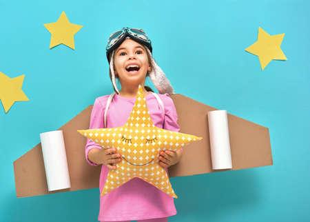 niña niño pequeño en un traje de astronauta está jugando y soñando con convertirse en un hombre del espacio. Retrato de niño divertido sobre un fondo de la pared azul brillante con las estrellas amarillas. Foto de archivo
