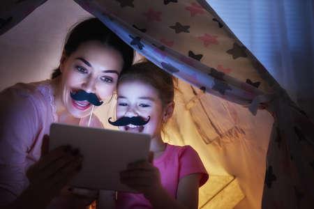 幸せな愛情のある家族。若い母親と彼女の娘の女の子は、就寝時に子供部屋で遊んでください。面白いママと素敵な子は、タブレットで楽しんでい