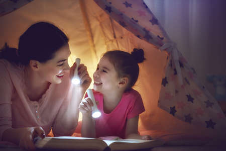 flashlights: Family bedtime. Mom and child daughter are reading a book with flashlights in tent. Pretty young mother and lovely girl having fun in children room. Stock Photo