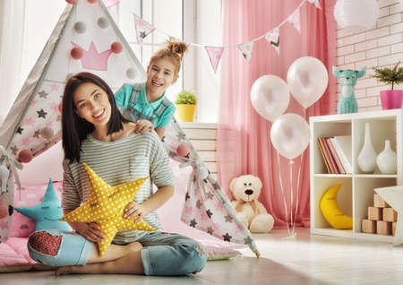 cute little girl: Happy loving family. Mother and her daughter girl play in children room. Funny mom and lovely child having fun indoors.