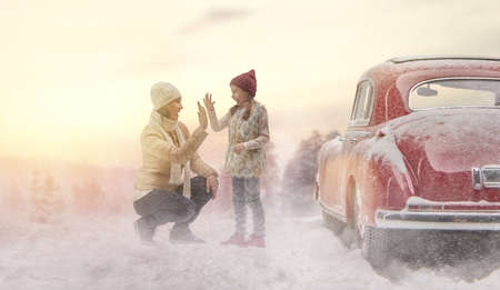 vintage car: Toward adventure! Happy family are relaxing and enjoying road trip. Mother, child and vintage car on snowy winter nature background. Christmas holidays time.