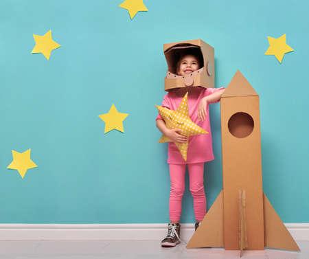 グッズ ロケット、宇宙飛行士になる夢を再生と宇宙飛行士コスチューム子供女の子。黄色の星と明るい青い壁の背景に面白い子供の肖像画。 写真素材