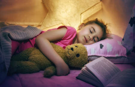 asleep: Adorable little child girl is napping in the tent. Quiet sleep with teddy bear after reading book.
