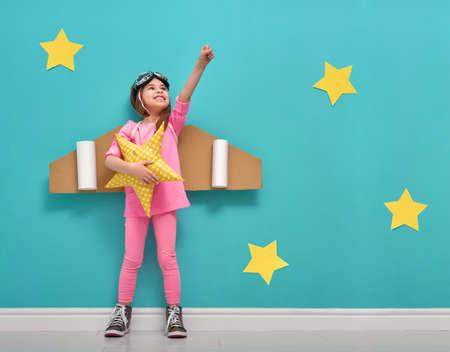 Dziewczynka dziecka w stroju astronauty bawi i marzy o zostaniu astronautą. Portret Zabawna dziecko na tle jasnej niebieskiej ścianie z żółtymi gwiazdami.