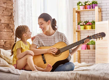girl home: Happy family. Mother and daughter together. Adult woman playing guitar for child girl.
