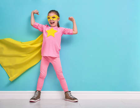 Little child plays superhero. Kid on the background of bright blue wall. Girl power concept. Yellow, pink and  turquoise colors. Stok Fotoğraf