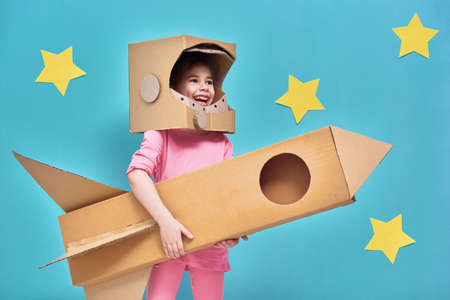 Child girl in an astronaut costume with toy rocket playing and dreaming of becoming a spacemen. Portrait of funny kid on a background of bright blue wall with yellow stars.
