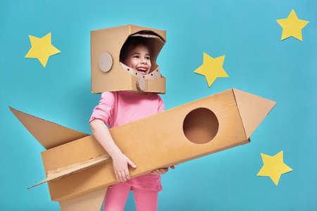 Kindmeisje in een astronautenkostuum met stuk speelgoed raket die en van ruimtijden spelen spelen dromen. Portret van grappig jong geitje op een achtergrond van heldere blauwe muur met gele sterren.