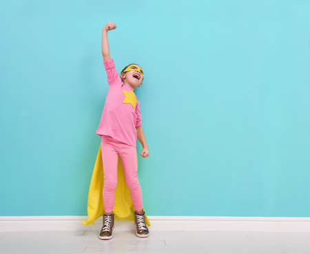 Little child plays superhero. Kid on the background of bright blue wall. Girl power concept. Yellow, pink and  turquoise colors. Stock Photo