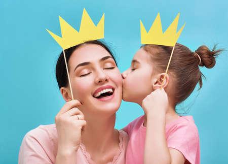 Familia divertida en un fondo de la pared azul brillante. La madre y su hija niña con accesorios de papel. Madre y el niño están sosteniendo corona de papel en el palillo.
