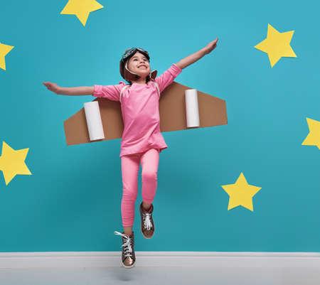 宇宙飛行士のコスチュームの子少女は再生、宇宙飛行士になることを夢見てします。黄色の星と明るい青い壁の背景に面白い子供の肖像画。