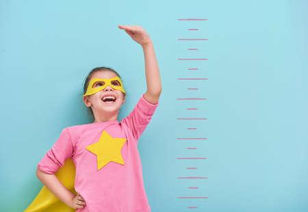 小さな子供は、スーパー ヒーローを果たしています。子供は、明るい水色の壁の背景に成長を測定します。女の子力の概念。黄色、ピンク、ターコ 写真素材