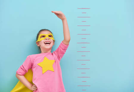 작은 아이는 슈퍼 히어로을한다. 아이는 밝은 파란색 벽의 배경에 성장을 측정합니다. 여자 전원 개념입니다. 노란색, 분홍색과 터키석 색.