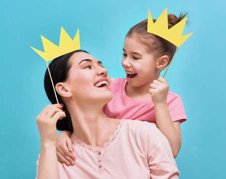 밝은 파란색 벽의 배경에 재미있는 가족. 어머니와 딸이 종이 액세서리와 함께 소녀. 엄마와 아이 스틱에 종이 왕관을 들으십시오.