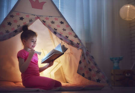 study: Cute little child is reading a book with flashlights in tent. Happy girl plays at home. Funny lovely kid having fun in children room. Stock Photo