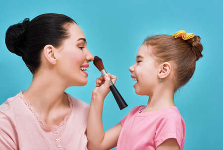 Funny family on a background of bright blue wall. Mother and her daughter girl are doing your makeup and having fun. Yellow, pink and turquoise colors. Stok Fotoğraf