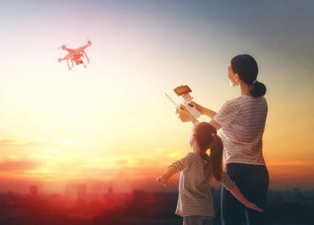 Little girl and her mother are operating the drone by remote control in the park. Kid and mom are playing with quadrocopter outdoors. Stock Photo