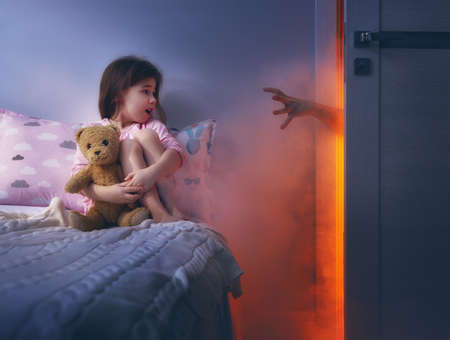 Nightmare for children. Little child girl is afraid of monsters in the dark of night.