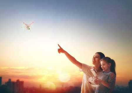 Little girl and her mother are operating the drone by remote control in the park. Kid and mom are playing with quadrocopter outdoors. Zdjęcie Seryjne