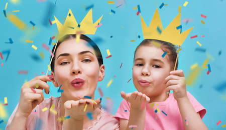 Funny family on a background of bright blue wall. Mother and her daughter girl blow confetti. Mom and child are holding paper crowns on stick. Stok Fotoğraf