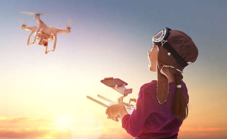Little girl is operating the drone by remote control in the park. Kid is playing with quadrocopter outdoors. Stockfoto