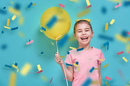 明るい水色の壁の背景に面白い子。女の子が風船と紙吹雪で楽しんでください。黄色、ピンク、ターコイズの色。 写真素材 - 69994290