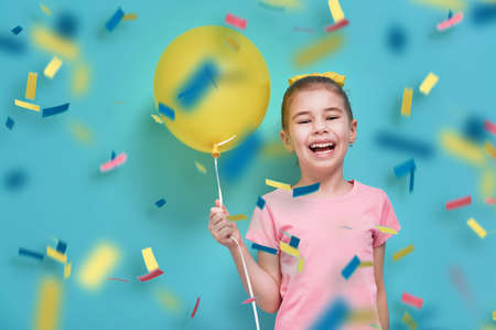 Funny child on a background of bright blue wall. Girl is having fun with balloons and confetti. Yellow, pink and turquoise colors. Imagens - 69994290