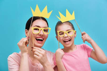 Familia divertida en un fondo de la pared azul brillante. La madre y su hija niña con accesorios de papel. Madre y el niño son la celebración de las gafas y coronas en el palillo. Foto de archivo - 69994293