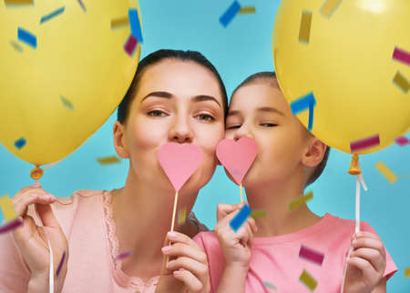 Funny family on a background of bright blue wall. Mother and her daughter girl are having fun with balloons and confetti. Yellow, pink and turquoise colors.