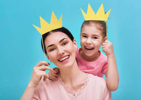 Grappige familie op een achtergrond van heldere blauwe muur. Moeder en haar dochter meisje met een papieren accessoires. Moeder en kind houden kroon op stok.