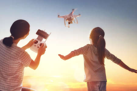 Little girl and her mother are operating the drone by remote control in the park. Kid and mom are playing with quadrocopter outdoors.