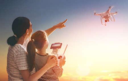 小さな女の子と彼女の母親は、公園でリモコンでドローンを操作が。子供とお母さんは、quadrocopter アウトドアで遊んでいます。