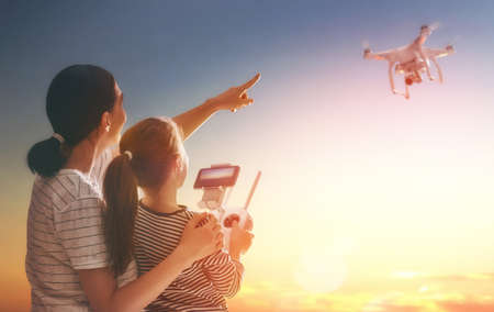 Little girl and her mother are operating the drone by remote control in the park. Kid and mom are playing with quadrocopter outdoors. Imagens - 70912074