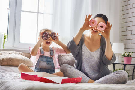 Happy loving family. Mother and her daughter child girl are eating donuts and having fun on the bed in the room.