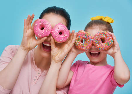 Funny family on a background of bright blue wall. Mother and her daughter girl are having fun with colorful donuts. Dieting concept and junk food. Yellow, pink and turquoise colors. Stock Photo
