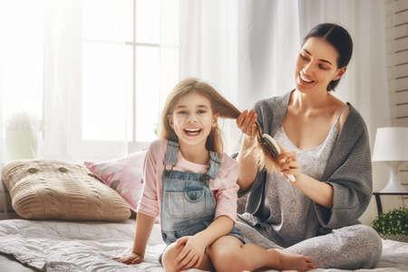 幸せな愛情のある家族。母は部屋のベッドの上に座っている彼女の娘の髪をとかすこと。