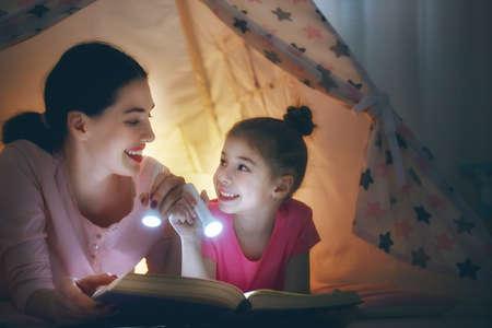 coricarsi famiglia. Mamma e figlia figlio stanno leggendo un libro con le torce elettriche in tenda. Piuttosto giovane madre e bella ragazza divertirsi in camera dei bambini.